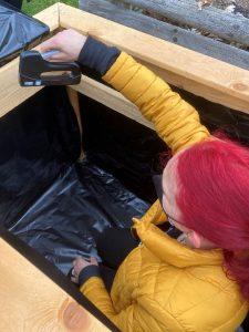 Schülerin beim Befestigen der Folie in einem Hochbeet.