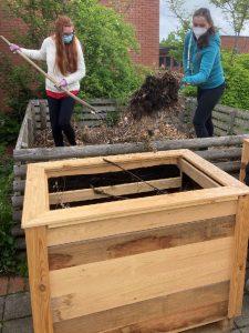 Schülerinnen beim Beschicken des Hochbeetes mit Kompost.
